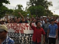 "Central American migrants taking part in a caravan called ""Migrant Viacrucis"" towards the United States raise their fists and hold a banner reading ""Emigrant Viacrucis 2018. We are all America. No to discrimination"" as they march to protest against US President Donald Trump's policies in Matias Romero, Oaxaca State, Mexico, …"