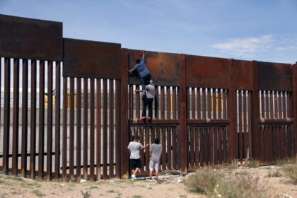 A young Mexican helps a compatriot to climb the metal wall that divides the border between Mexico and the United States to cross illegally to Sunland Park, from Ciudad Juarez, Chihuahua state, Mexico on April 6, 2018. US President Donald Trump on April 5, 2018 said he would send thousands …