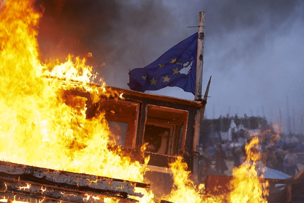 The remains of a small boat flying European flags is burnt on a bonfire during a demonstration in Whitstable, southeast England on April 8, 2018 against the Brexit transition deal that would see Britain continue to adhere to the Common Fisheries Policy after formally leaving the EU.
