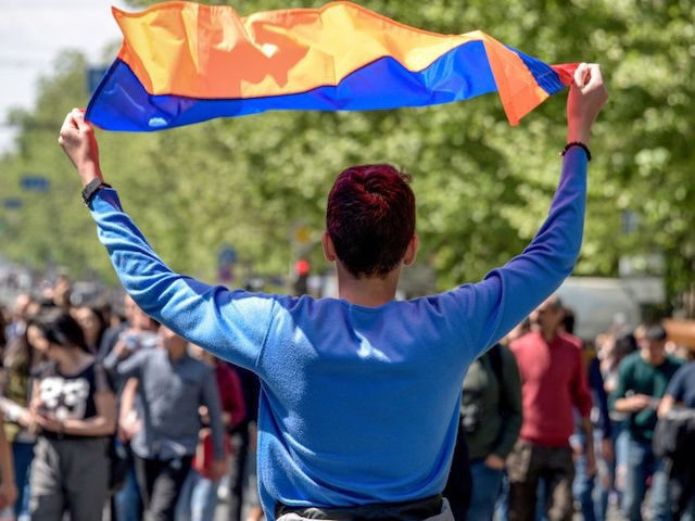 A man holds an Armenian national flag during an opposition rally in central Yerevan on April 18, 2018. Thousands of people rallied in Armenia's capital on April 18 to protest the election of former president Serzh Sarkisian as prime minister, viewed by the opposition as a power grab. / AFP …