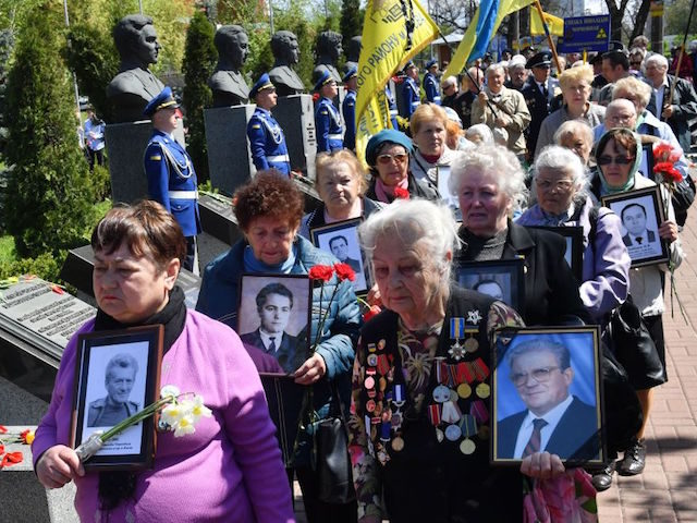 "Widows carry the pictures of their late husbands, who were ""liquidators"" in Chernobyl, during a ceremony in tribute to the victims of the Chernobyl nuclear disaster which occured 32 years ago, at a memorial to victims in Kiev, on April 26, 2018. - The accident spread radioactive fallout across Europe …"