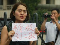 "FILE - In this Aug. 1, 2016 file photo, a man films Li Wenzu, left, wife of imprisoned lawyer Wang Quanzhang, holds a paper that reads ""Release Liu Ermin"" as she and supporters of a prominent Chinese human rights lawyer and activists stage a protest outside the Tianjin No. 2 …"