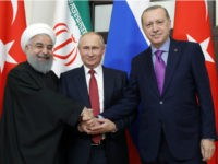 Russian President Vladimir Putin flanked by Turkish President Recep Tayyip Erdogan (r) and Iranian President Hassan Rouhani pose during a trilateral meeting on Syria in Sochi last November