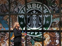 In this Tuesday, March 21, 2017, file photo, a woman walks past a Starbucks coffee shop in Sewickley, Pa. Starbucks Corp. reports earnings Thursday, Jan. 25, 2018. (AP Photo/Gene J. Puskar, File)