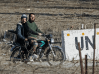A picture taken from the Israeli-occupied Golan Heights shows armed men, reportedly rebel fighters, driving a motorcycle near an abandoned UN building in the Syrian side of the Golan Heights, at an abandoned UN base at the Quneitra border crossing, on November 28, 2016. Israel's air force targeted gunman linked …