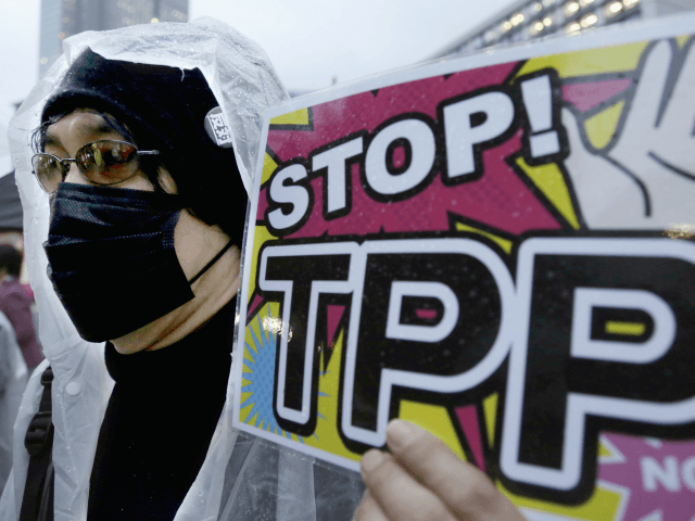 In this April 22, 2104 file photo, a protester holds a placard during a rally against the Trans-Pacific Partnership (TPP) in Tokyo. Donald Trump and Hillary Clinton agree on almost nothing. Except for their dislike of a sweeping agreement that would erase most tariffs and other trade barriers among the …