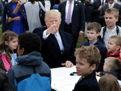 U.S. President Donald Trump (C) points to members of the news media while writing messages to military troops during the 140th annual Easter Egg Roll on the South Lawn of the White House April 2, 2018 in Washington, DC. The White House said they are expecting 30,000 children and adults …