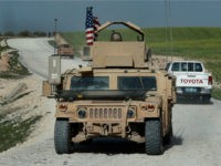 In this picture taken on Thursday, March 29, 2018, U.S. troop's humvee passes vehicles of fighters from the U.S-backed Syrian Manbij Military Council on a road leading to the tense front line with Turkish-backed fighters, at Halawanji village, north of Manbij town, Syria. The front line has grown more tense …