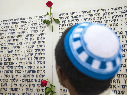 An Israeli man prays in front of a commemorative plaque celebrating fallen soldiers and decorated with roses at the Armored Corps memorial, following a ceremony to mark Remembrance Day (or Memorial Day) on May 5, 2014 at Latrun Junction, near Jerusalem. Israel is marking Remembrance Day to commemorate the fallen …
