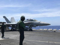 Crewmen of the U.S. aircraft carrier Theodore Roosevelt prepare their aircraft Tuesday, April 10,2018 in international waters off South China Sea. The aircraft carrier Theodore Roosevelt (CVN-71) is sailing through the disputed South China Sea in the latest display of America's military might after China built a string of islands with military facilities in the strategic sea it claims almost in its entirety. (AP Photo/Jim Gomez)