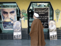 An Iranian clergyman passes anti-Israeli posters, during activities marking the 10th anniversary of the assassination of the late Palestinian Islamic Jihad leader, Fathi Shaqaqi in Tehran, 30 October 2005. Iran's hardline President Mahmoud Ahmadinejad insisted today that his controversial call for Israel to be 'wiped off the map' was nothing …