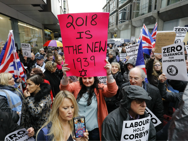 People hold up placards and Union flags as they gather for a demonstration organised by the Campaign Against Anti-Semitism outside the head office of the British opposition Labour Party in central London on April 8, 2018. Labour leader Jeremy Corbyn has been under increasing pressure to address multiple allegations of …