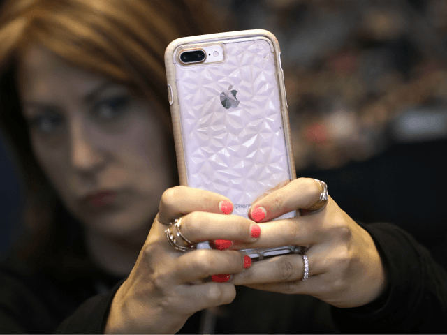 A customer uses her Apple iPhone X during an Apple event at their main store Tuesday, March 27, 2018, in Chicago. (AP Photo/Charles Rex Arbogast)