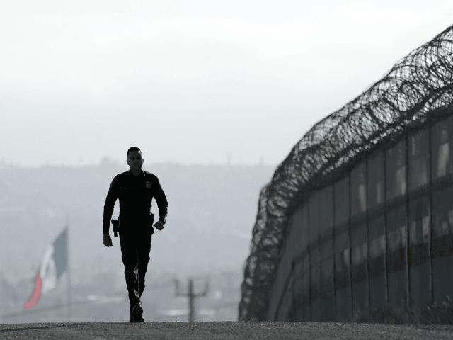 In this Wednesday, June 22, 2016 photo, Border Patrol agent Eduardo Olmos walks near the secondary fence separating Tijuana, Mexico, background, and San Diego in San Diego. The Supreme Court deadlocked Thursday on President Barack Obama's immigration plan that sought to shield millions living in the U.S. illegally from deportation, …