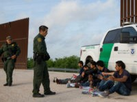 Border Patrol agents apprehend illegal immigrants shortly after they crossed the border from Mexico into the United States on Monday, March 26, 2018 in the Rio Grande Valley Sector near McAllen, Texas. An estimated 11 million undocumented immigrants live in the United States, many of them Mexicans or from other Latin American countries. / AFP PHOTO / Loren ELLIOTT (Photo credit should read LOREN ELLIOTT/AFP/Getty Images)