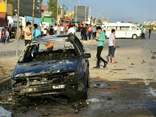 Iraqis check the damage at the site of an attack involving a moped laden with explosives against a convoy carrying an Iraqi election candidate in the city of Kirkuk, a multiethnic flashpoint some 250 kilometres (155 miles) north of Baghdad, on April 15, 2018. / AFP PHOTO / Marwan IBRAHIM …