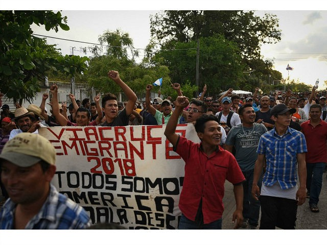 Central American migrants taking part in a caravan called 'Migrant Viacrucis' towards the United States raise their fists and hold a banner reading 'Emigrant Viacrucis 2018. We are all America. No to discrimination' as they march to protest against US President Donald Trump's policies in Matias Romero, Oaxaca State, Mexico, …