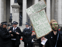 British policemen (L) share a joke as a man protests against Climate Change, Poverty and Injustice and Suffering, outide the Royal Exchange in London, on March 31, 2009. London is bracing for angry protests before and during Thursday's G20 summit, which will see fortress-like security for world leaders including US …