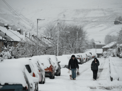 A couple walk through the snow in the village of Marsden, east of Manchester in northern England on April 2, 2018, after a return of wintry weather brought snow showers to parts of northern England. / AFP PHOTO / OLI SCARFF (Photo credit should read OLI SCARFF/AFP/Getty Images)