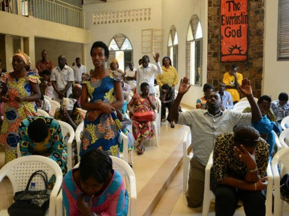 People pray inside an Evangelical restoration church on April 6, 2014, in Kigali, on the eve of the start of a national mourning period marking the 20th anniversary of the 1994 genocide against the Tutsi in Rwanda. Rwanda on April 6 called on France to face up to the 'difficult …