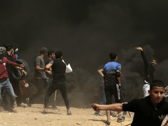 Palestinian protestors try to take down a section of barbed wire at the border fence with Israel, east of Gaza City in the central Gaza Strip, on April 13, 2018. Clashes erupted as thousands protested for a third consecutive Friday along Gaza's border with Israel after violence in which Israeli …