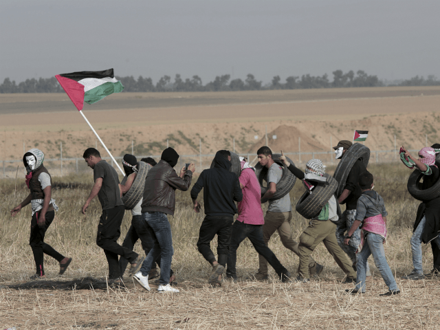 Palestinian masked protesters carrying tires walk toward the border fence during clashes with Israeli troops along Gaza's border with Israel, east of Khan Younis, Gaza Strip, Thursday, April 5, 2018. An Israeli airstrike in northern Gaza early on Thursday killed a Palestinian, while a second man died from wounds sustained …
