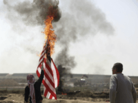 Palestinian protesters burn an American flag during a protest at the Gaza Strip's border with Israel, Friday, April 6, 2018.