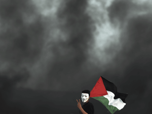 A protester holding a Palestinian flag flashes the victory sign for a photographer during a protest at the Gaza Strip border with Israel, in eastern Gaza City, Wednesday, April 4, 2018. A leading Israel human rights group urged Israeli forces in a rare step Wednesday to disobey open-fire orders unless …