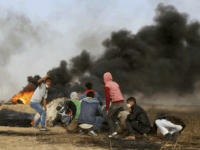 Palestinian protesters cover during clashes with Israeli troops along Gaza's border with Israel, east of Khan Younis, Gaza Strip, Thursday, April 5, 2018. An Israeli airstrike in northern Gaza early on Thursday killed a Palestinian, while a second man died from wounds sustained in last week's mass protest. The fatalities …