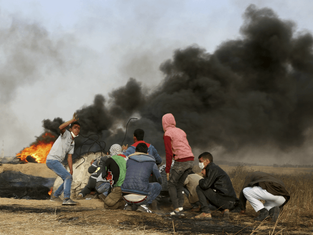 Palestinian protesters cover during clashes with Israeli troops along Gaza's border with Israel, east of Khan Younis, Gaza Strip, Thursday, April 5, 2018. An Israeli airstrike in northern Gaza early on Thursday killed a Palestinian, while a second man died from wounds sustained in last week's mass protest. The fatalities bring to 21 the number of people killed in confrontations in the volatile area over the past week with a new round of protests along the border is expected on Friday. (AP Photo/Adel Hana)