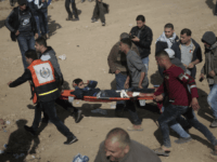 Palestinian protesters carry a wounded youth who was shot by Israeli troops during a demonstration near the Gaza Strip border with Israel, in eastern Gaza City, Friday, March 30, 2018. (AP Photo/ Khalil Hamra)