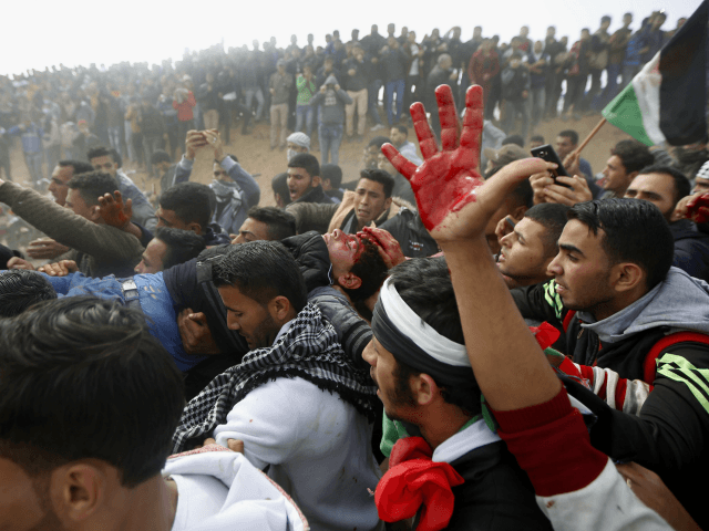 Palestinian protesters evacuate a wounded youth during clashes with Israeli troops along the Gaza Strip border with Israel, east of Khan Younis, Gaza Strip, Friday, March 30, 2018. (AP Photo/Adel Hana)