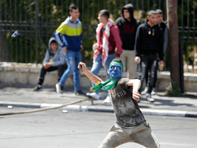 A Palestinian protester hurls stones towards Israeli border police officers during clashes in the West Bank city of Bethlehem, Saturday, March 31, 2018. Israel's chief military spokesman says if violence drags on along the Gaza border, Israel will expand its reaction to strike the militants behind it. (AP Photo/Nasser Shiyoukhi)