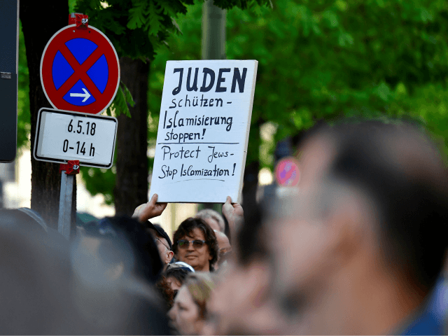 A protester holds a placard during the 'Berlin wears kippa' event, with more than 2,000 Jews and non-Jews wearing the traditional skullcap to show solidarity with Jews on April 25, 2018 in Berlin after Germany has been rocked by a series of anti-Semitic incidents. - Germans stage shows of solidarity …