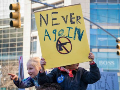View of a young demonstrator, on someone's shoulders, as she holds a sign that reads 'Never Again' during the March For Our Lives rally against gun violence, near Columbus Circle, New York, New York, March 24, 2018. Beside her, another girl points her finger. (Photo by Barbara Alper/Getty Images)
