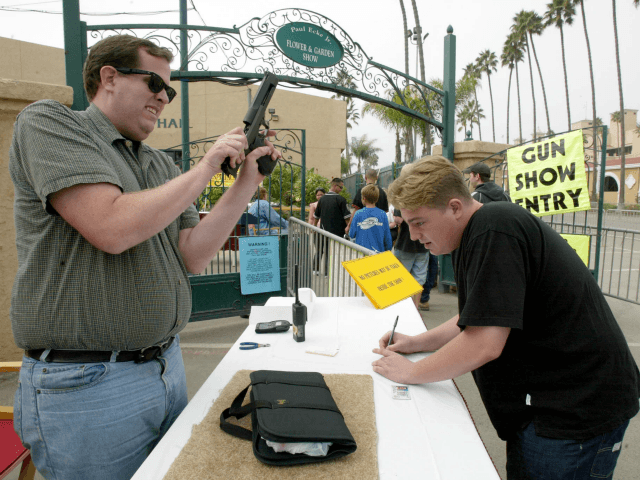 A man checks a handgun at the reception desk of the Cross Roads of the West Gun Show in Del Mar, California, 20 October, 2002, where loade guns are not allowed. The show is being held several times a year in dozens of cities in the West Coast and gathers …