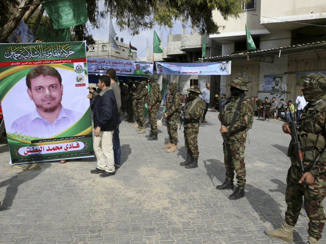 Relatives sit up a photo while masked militants from the Izzedine al-Qassam Brigades, a military wing of Hamas, receive condolences at the house mourning of engineer Fadi al-Batsh, who was killed assassinated in Malaysia this morning, in front of his family house in Jebaliya, Gaza Strip, Saturday, April 21, 2018. …