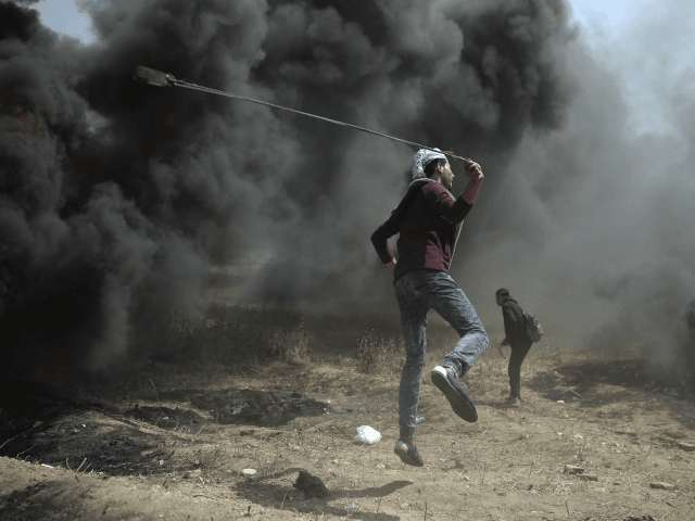 A Palestinian protester hurls stones at Israeli troops during a protest at the Gaza Strip's border with Israel, Friday, April 6, 2018. (AP Photo/ Khalil Hamra)