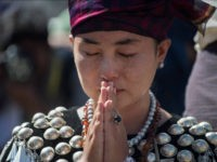 A woman wearing traditional dress from Kachin state in Myanmar sheds a tear as she prays outside St. Mary's Cathedral during a mass led by Pope Francis in Yangon during his last day of a four-day visit on November 30, 2017. Pope Francis on November 30 wrapped up a visit …