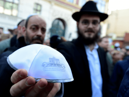 A man shows a kippa during the 'Berlin wears kippa' event, with more than 2,000 Jews and non-Jews wearing the traditional skullcap to show solidarity with Jews on April 25, 2018 in Berlin after Germany has been rocked by a series of anti-Semitic incidents. - Germans stage shows of solidarity …