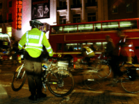 An officer of the Metropolitan Police on bicycle watches approximately 200 cyclist sympathisers of the Critical Mass cyclists`group make their way from the South Bank and along the Strand past the theatre district, 28 October 2005 in London, United Kingdom. Critical Mass, who have made the same journey every month …