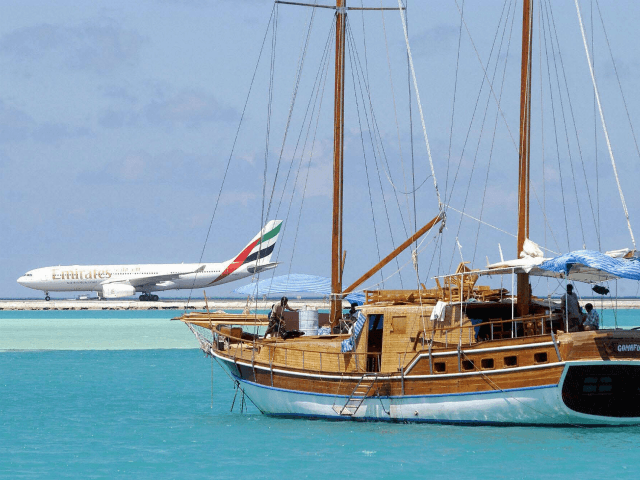 In this picture taken on October 18, 2003, An aeroplane lands at Male International Airport while a sail boat makes its way through a blue lagoon. The exotic Maldives, one of the world's most exclusive tourist destinations, is looking to cut prices and put resort expansion on hold to weather …