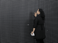 "Janine Fisher of Pittsburgh looks at an art installation called ""Prescribed to Death Memorial"" at the William Pitt Union at the University of Pittsburgh on Wednesday, Jan. 31, 2018 in Pittsburgh. The installation features 22,000 carved medicine pills that represent the face of someone who fatally overdosed in 2015. A creation of the Illinois-based National Safety Council, the memorial is making it's inaugural stop in Pittsburgh through Friday. Future stops will be in Ohio, Oklahoma, Tennessee, Georgia, and New York. (AP Photo/Gene J. Puskar)"