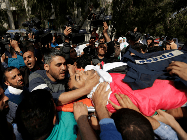 Mourners and journalists carry the body of Palestinian journalist Yasser Murtaja, during his funeral in Gaza City on April 7, 2018. Among those killed at Friday's protest was Yasser Murtaja, a photographer with the Gaza-based Ain Media agency, who died from his wounds after being shot, the local health ministry said. Murtaja's company confirmed his death, with witnesses saying he was close to the front of the protests in Southern Gaza when he was hit. / AFP PHOTO / MAHMUD HAMS (Photo credit should read MAHMUD HAMS/AFP/Getty Images)