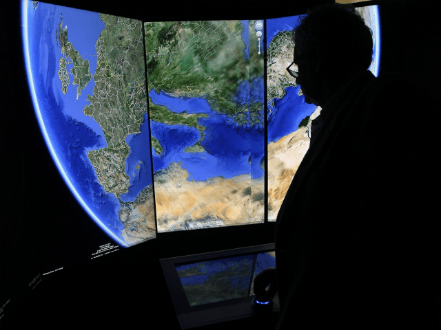 A visitor looks at a three-dimensional rendering of the planet Earth while using Google Earth software on September 26, 2012 at the official opening party of the Google offices in Berlin, Germany. Although the American company holds 95% of the German search engine market share and already has offices in …
