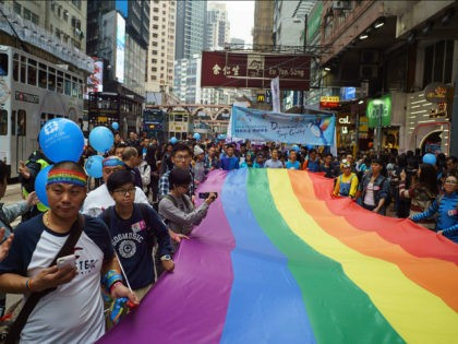 Participants of Hong Kong's annual pride parade march with a giant rainbow flag on November 25, 2017. Rainbow flags flowed through the streets of Hong Kong on November 25 during the city's annual pride parade, as LGBT activists criticised authorities for lagging behind on equal rights. / AFP PHOTO / …