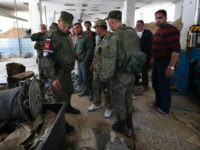 Russian military police officers check weapons left behind by members of the Army of Islam group in a factory produced weapons, in the town of Douma, the site of a suspected chemical weapons attack, near Damascus, Syria, Monday, April 16, 2018. Faisal Mekdad, Syria's deputy foreign minister, said on Monday …