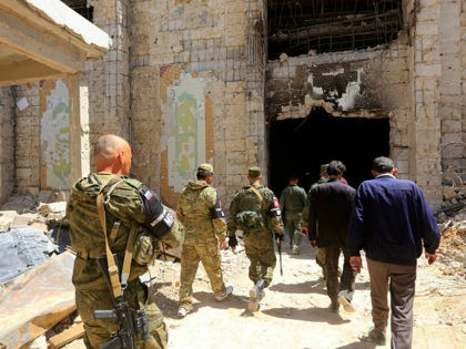 Russian forces patrol damaged buildings in Douma, Syria on the outskirts of Damascus on April 16, 2018 during an organised media tour after the Syrian army declared that all anti-regime forces have left Eastern Ghouta, following a blistering two month offensive on the rebel enclave. The announcement, which represents a …