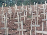 Rwandan women walk along a path next to a mass grave holding hundreds of victims of the 1994 genocide Saturday, Sept. 7, 1996 outside Kigali, Rwanda. An International Criminal Tribunal for Rwanda will begin genocide trials in Arusha, Tanzania Sept. 26, 1996. (AP Photo/David Guttenfelder)