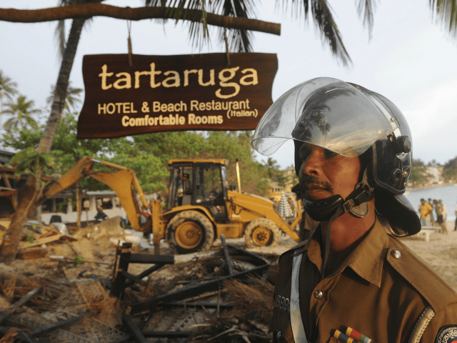 A Sri Lankan police officer looks on near a demolished illegally built Sri Lankan hotel that was bulldozed in the southern town of Unawatuna on December 13, 2011. Sri Lanka is experiencing a boom in tourism after security forces crushed the Tamil Tiger rebels in May 2009, ending 37-years of …